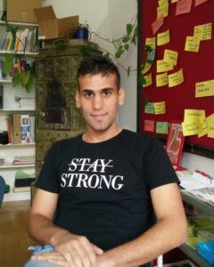 """Ahmed Alqaysi zu Gast im KUPFbüro. Auf seinem T-Shirt steht """"STAY STRONG"""", das """"STAY"""" ist durchgestrichen."""