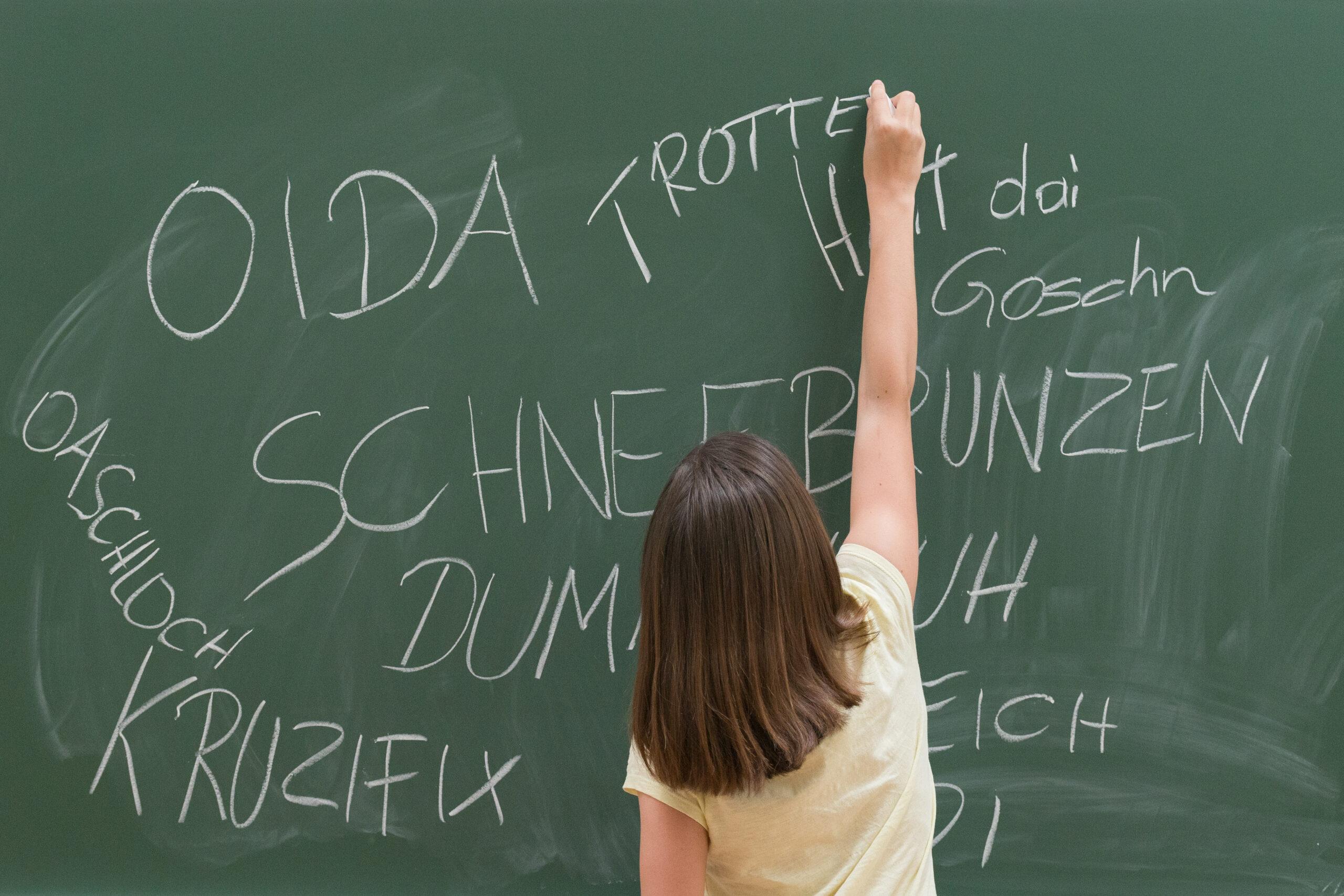 Kind schreibt Schimpfwörter auf die Schultafel