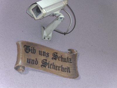 """Überwachungskamera + Graffiti/Lüftlmalerie """"Gib uns Schutz und Sicherheit"""""""