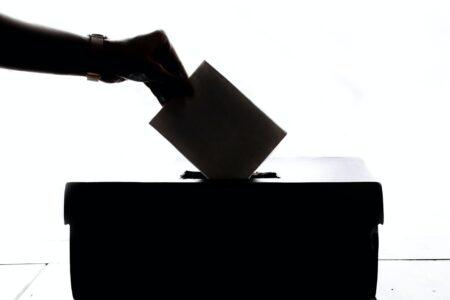 Hand wirft Wahlzettel in Urne